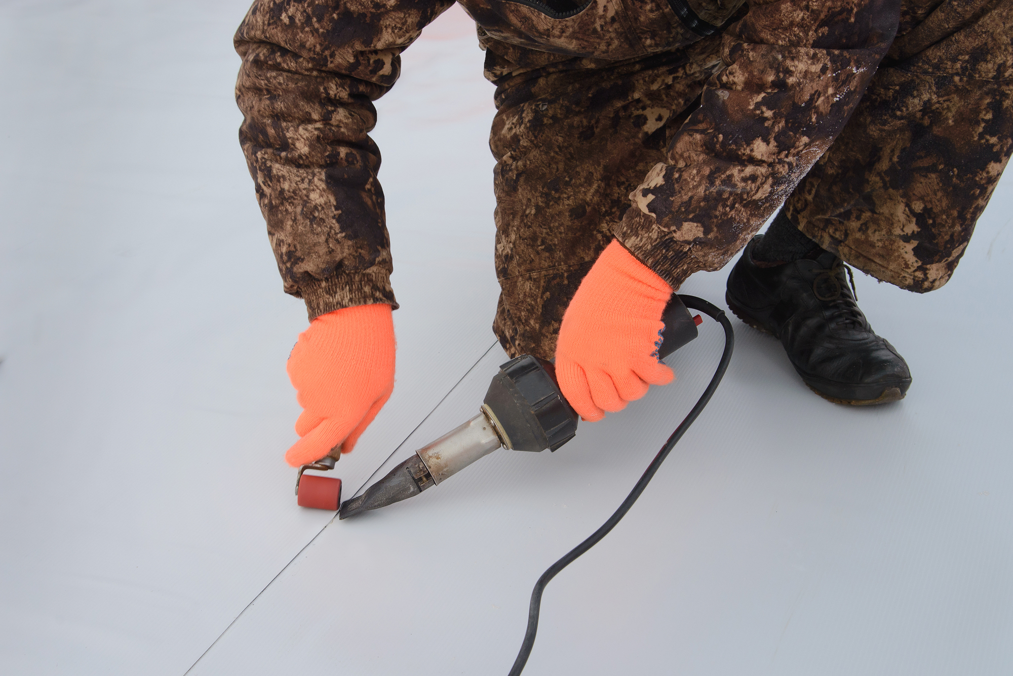 Waterproofing and insulation at construction site, roof sealing process of synthetic membrane with Hot Air Hand Tool. New protection technology. Closeup